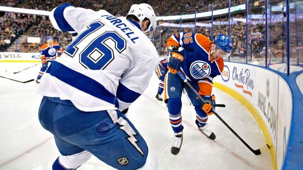 Teddy Purcell of the Tampa Bay Lightning battles in the corner with Martin Marincin of the Edmonton Oilers in NHL action on Jan. 5, 2014. Purcell will now join the Oilers for the 2014-15 season, after being traded by Lightning.