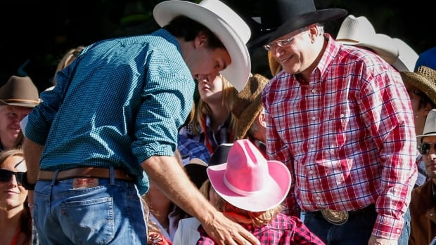 Prime Minister Stephen Harper, right, meets Liberal leader Justin Trudeau, left, and his daughter Ella-Grace at the Calgary Stampede parade Friday. Harper used a speech at his annual barbecue for supporters in Calgary on Saturday to attack Trudeau as a big-spending liberal without substance.