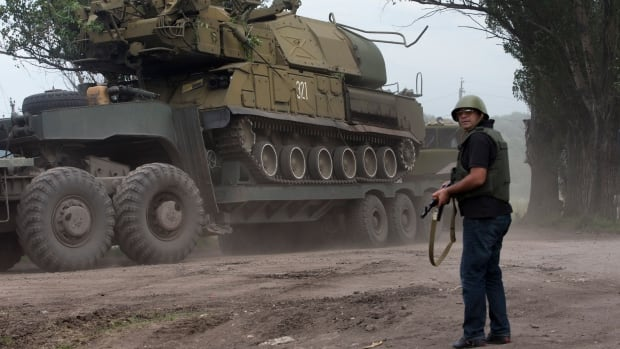 Ukrainian government forces head for the fighting in the eastern side of the country with an anti-aircraft missile launcher.