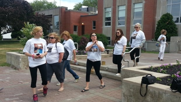 Members of the Dagenais family leave court after Blake Lapierre was found guilty of manslaughter, but not guilty of murder, in the 2012 death of Justin Dagenais. Family members wore shirts printed with pictures of Dagenais.