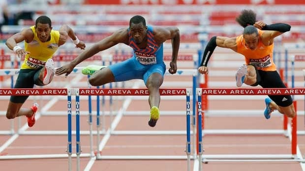 Hansle Parchment of Jamaica, centre, clears a hurdle as he competes with Pascal Martinot-Lagarde of France, right, and Orlando Ortega of Cuba, left, in men's hurdles on Saturday.