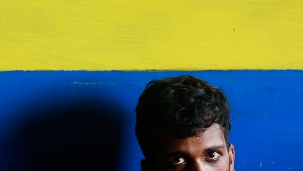 "A would-be illegal asylum seeker from Sri Lanka waits at a police station in Colombo in 2012, after being arrested for attempting to sail to Australia illegally by boat. In a statement on Monday, 53 Australian legal scholars said Australia's policy toward asylum seekers ""raises a real risk"" of breaching Australia's obligations under international refugee and human rights law."