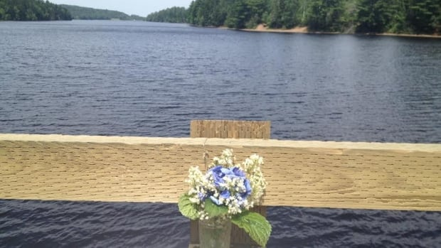 Flowers are placed at the spot where Alex Kennedy Jones jumped off a bridge into the water Friday evening off Black River Road.