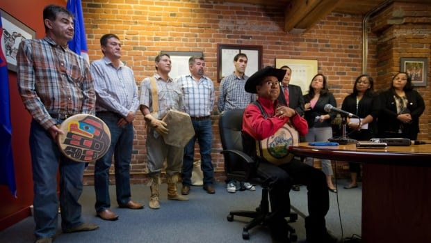 Chief Roger William, right, of the Xeni Gwet'in First Nation is flanked by chiefs and other officials as he pauses while speaking during a news conference in Vancouver after the Supreme Court of Canada ruled in favour of the Tsilhqot'in First Nation, granting it land title to 438,000 hectares of land.