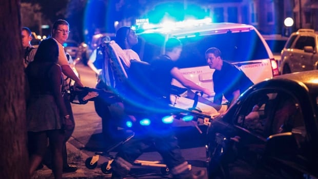 A Chicago man who was shot in the leg on Sunday, July 6 is taken away on a stretcher. The city had more than 50 shootings on the Independence Day holiday weekend, which saw 14 killed and dozens more wounded.