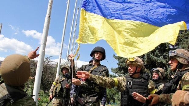 Ukrainian soldiers and Ukrainian Defence Minister Valery Heletey, third from right, raise a Ukrainian flag in downtown Slovyansk. After Ukrainian forces' seizure of a key rebel stronghold in the east, the major cities of Donetsk and Luhansk could be the next focus of major fighting.