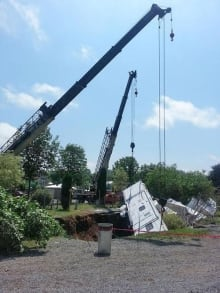 Cranes haul a trailer out of a sinkhole caused by Arthur at a Fredericton RV park