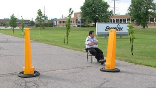 A security guard sits outside Energizer's Notre-Dame Street East plant Tuesday after its 2017 closure was announced to its 430 employees on Tuesday.