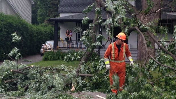 Hydro-Québec worker Cedric Chaperon clears debris as Morgan Chenu and her three-year-old daughter Nell look on. Chenu, who lives in Pointe-Claire, has been without power since about 10 p.m. She says she's lucky the tree branch didn't hit her house.