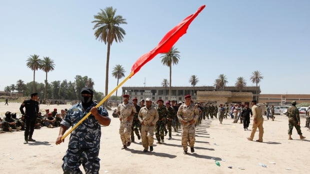 Shia volunteers march during training in Baghdad. Iraqi security forces found 53 corpses, blindfolded and handcuffed, in a town south of Baghdad early on Wednesday.