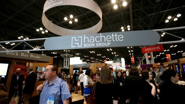 Visitors walk through the Hachette Book Group's exhibition at BookExpo America in New York this May. Hachette and Amazon are fighting over the price of e-books.