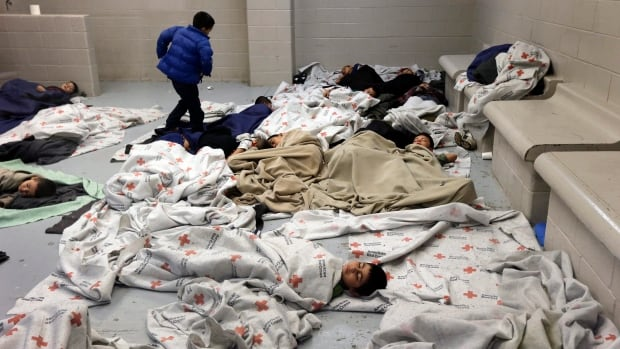 Detainees sleep in a holding cell at a U.S. Customs and Border Protection processing facility in Brownsville, Texas, on June 18, 2014.  Thousands of migrants, including 52,000 children, have crossed the border in recent months.