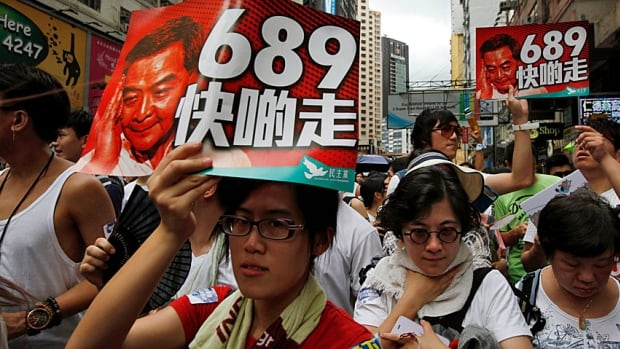 """Hong Kong protesters carry placards that read """"Go away quick"""" on a portrait of Hong Kong Chief Executive Leung Chun-ying and the number, 689, of those few electors who voted him in to office two years ago."""