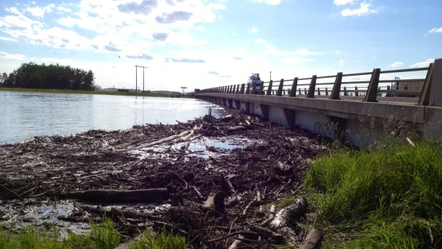 Debris from a rising Assiniboine River builds by on a bridge on the Trans-Canada Highway at the Portage Diversion on Wednesday evening.