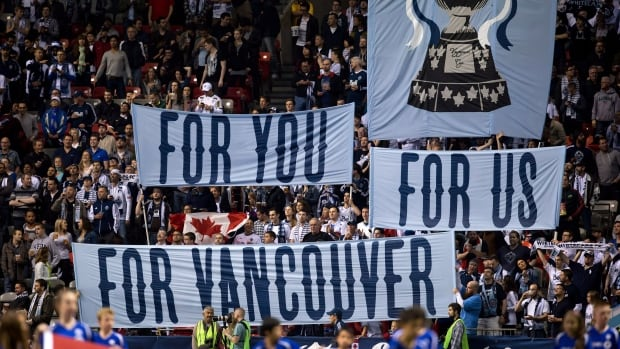 Fans hold up banners before the Vancouver Whitecaps and Montreal Impact play in the Canadian Championship soccer game in Vancouver, B.C., on Wednesday May 29, 2013.