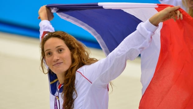 France's gold medalist Camille Muffat is seen here celebrating on the podium after the women's 400m freestyle swimming event at the London 2012 Olympic Games on July 29, 2012. Muffat has decided to retire at the age of 24.