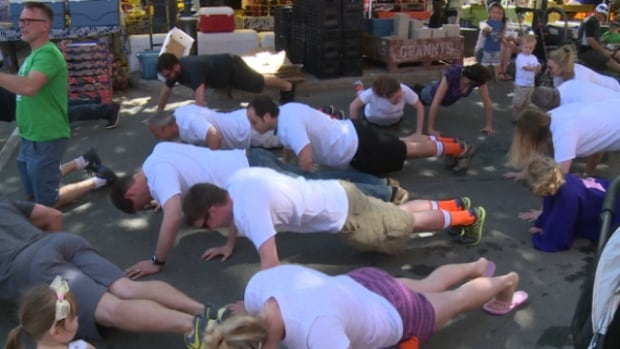 Dozens participated in the pushup flash mob at the Downtown Farmer's Market on Saturday.
