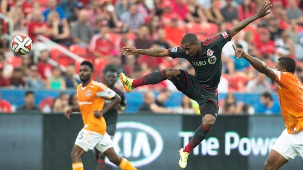 Toronto FC's Jermain Defoe, middle, leaps for a ball during the first half of Saturday night's MLS soccer match against the visiting Houston Dynamo. Defoe scored two goals and set up two others in Toronto's 4-2 victory.