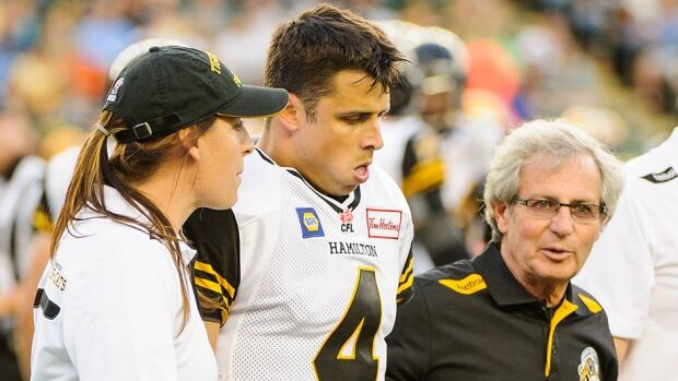 Tiger-Cats quarterback Zach Collaros, middle, is helped off the field during a July 4 game in Edmonton. He was flattened by a helmet hit to the chin and will sit out Friday's game at Calgary with head and back soreness.
