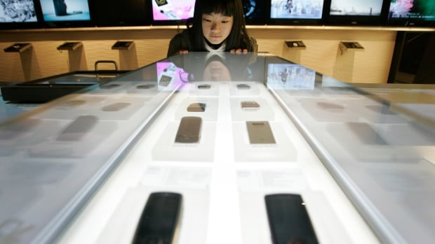 A student looks at Samsung mobile phones in a store in Seoul. Far from buying the company's products, a U.S. labour watchdog recently discovered children working in factories that make Samsung products.