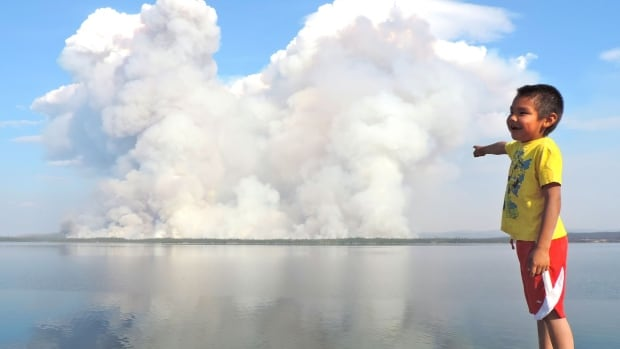 A boy points to a fire on the other side of a lake near Gameti, N.W.T. Mike Flannigan, a professor of wildland fire at the University of Alberta, says climate change is responsible for the hot, dry conditions that are causing fires to burn out of control.
