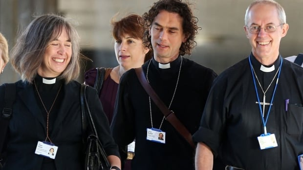 The Archbishop of Canterbury, Justin Welby, right, and unidentified members of the clergy, arrive for the General Synod meeting on Monday. The Church of England voted in favour of allowing women to enter its top ranks as bishops.