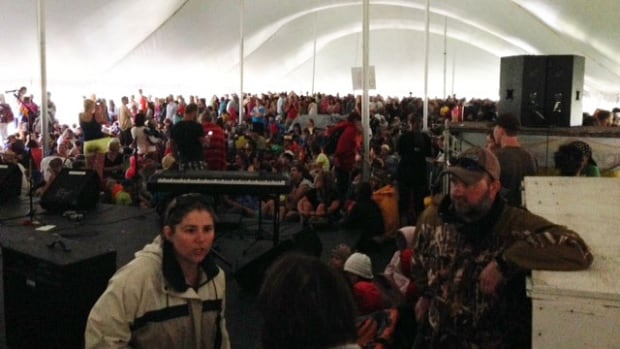 Festival-goers take cover in the children's tent as a storm hits on Saturday afternoon.