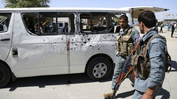 Afghan security personnel walk by a damaged vehicle after it was hit by a remote-controlled bomb on the outskirts of Kabul, Afghanistan, on Tuesday. The blast killed two passengers and also wounded five people, including the driver.