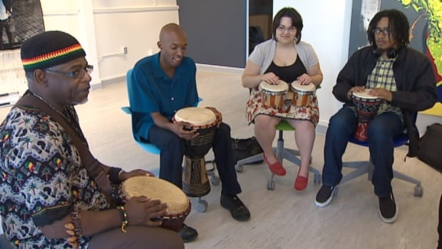 Henri Bishop (left) leads a drumming workshop, teaching young people the basics, and offering a little wisdom along the way.