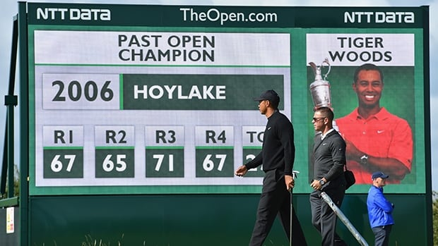 Tiger Woods and Canadian swing coach Sean Foley stroll by a billboard during Tuesday's practice round at Royal Liverpool.