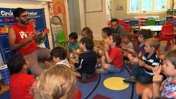 An educator leads children in song during a class at the Little Red Playhouse.