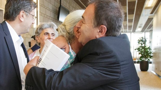 """A woman from the Bosnian town of Srebrenica is embraced by her lawyer at a civil court in The Hague, Netherlands, on Wednesday. A Dutch court has declared the country liable in the deaths of more than 300 Bosnian Muslim men murdered by Bosnian Serb forces in the United Nations-declared Srebrenica """"safe haven"""" 19 years ago."""