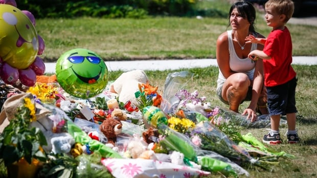 Jennifer Kohut and her son Axton, three, place flowers and a toy at an impromptu memorial for Nathan O'Brien and his grandparents at the Liknes home in Calgary.