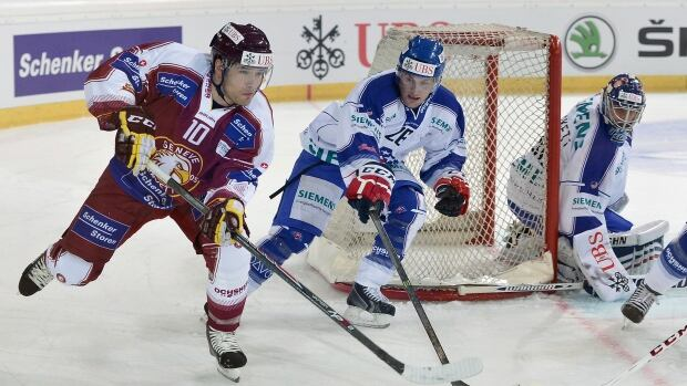 Geneva's Matthew Lombardi, left, challenges for the puck in a Spengler Cup game on Dec.  26, 2013.