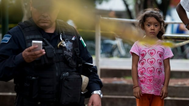A young girl waits with family outside of The Great Family Group Home to see loved ones who were rescued from horrific abuses after Mexican police raided the residence earlier this week.