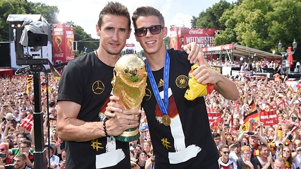Miroslav Klose, seen holding the Jules Rimet Trophy, and Erik Durm celebrate Germany's World Cup title in Berlin on Tuesday.