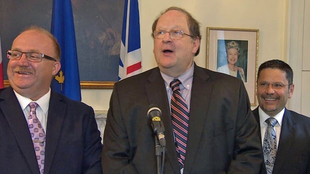 Premier Tom Marshall is flanked by new cabinet ministers Vaughn Granter (left) and Tony Cornect (right) at Government House in St. John's.