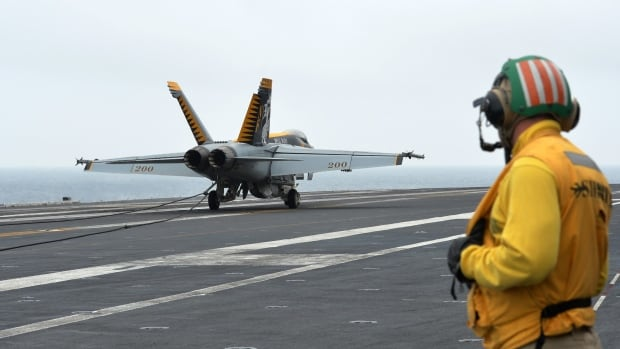 A U.S. F18 Hornet fighter attack aircraft lands on a U.S. aircraft carrier during a military exercise off South Korea's West Sea. North Korea on Monday fired a barrage of artillery shells into waters near its eastern sea border with the South.
