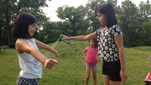 Sisters Kyla and Rihanna Pablo spray each other with insect repellent before a family picnic at Assiniboine Park on Thursday evening, after trap counts spiked.