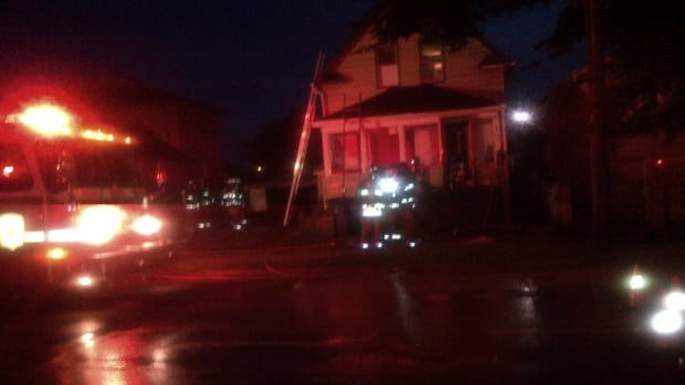Firefighters battle attic fire set by a lightning strike at this house on 20th St. W Thursday night in Saskatoon.