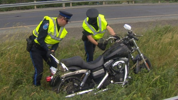Police handle a motorcycle in the median of the Outer Ring Road on Tuesday. The vehicle was left at the scene and was later stolen.