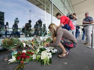 People place flowers outside Schiphol airport in Amsterdam, on July 18, 2014. The attack on a Malaysian jetliner Thursday afternoon killed 298 people from nearly a dozen nations, more than half being Dutch, including vacationers, students and a large contingent of scientists heading to an AIDS conference in Australia.