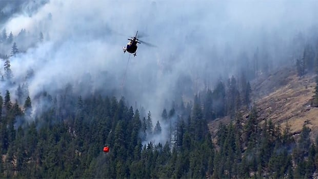 A helicopter drops fire retardant on the Smith Creek fire