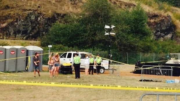 Festival-goers are seen being led away from the area where the body of Nick Phongsavath was discovered Friday.