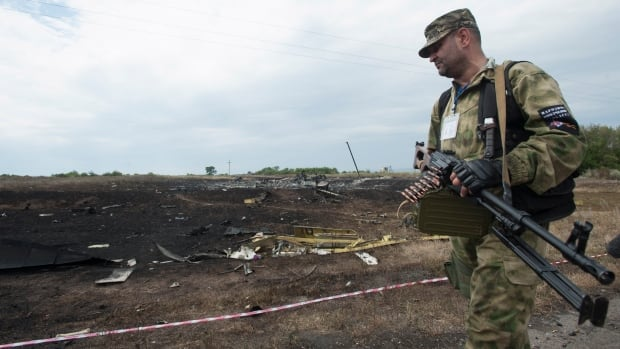 A pro-Russian fighter walks at the crash site of a Malaysia Airlines jet. Ukraine accused Russia on Saturday of helping separatist rebels destroy evidence at the crash site of Flight MH17 reportedly shot down in rebel-held territory - a charge the rebels denied.