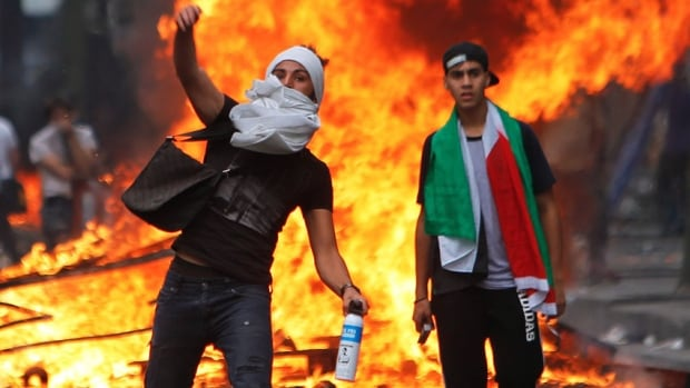 A pro-Palestinian demonstrator throws a stone towards riot police during a protest in Paris.