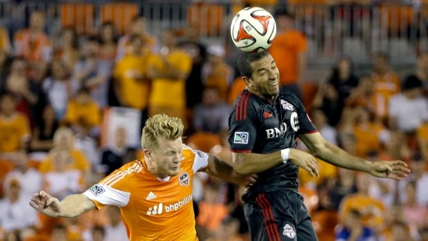 Houston Dynamo's Andrew Driver, left, and Toronto FC's Justin Morrow, right, go up for a header during the second half Saturday.