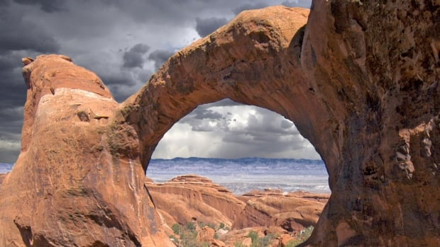 A composite image shows the Double O Arch before a storm at Devil's Garden, Arches National Park, in Utah. A new paper is the first to explain the mechanisms that stabilize sandstone landscapes into natural sculptures, according to the study's authors.