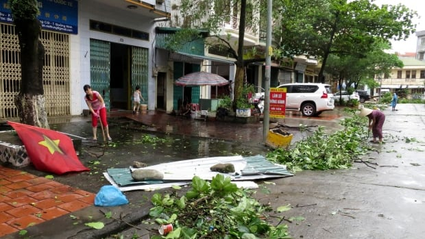Shop owners clear felled tree branches from the street after heavy rainfall from Typhoon Rammasun in Mong Cai, northern Vietnam, on July 19. The typhoon has killed dozens of people as it has swept through Asia, including at least 11 in Vietnam, 26 in southern China and 38 in the Philippines.