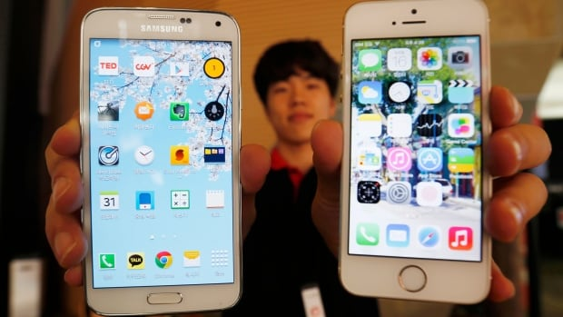 A sales assistant holds Samsung's Galaxy 5 smartphone, which has a 5-inch screen, and Apple Inc's iPhone 5 smartphone, which has a 4-inch screen, at a store in Seoul. Apple is widely expected to have a larger screen on its next generation of iPhone.